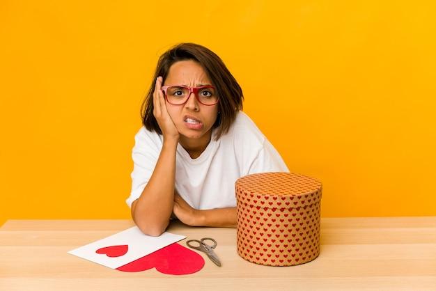 Junge hispanische frau, die ein valentinsgeschenk vorbereitet, isoliert isoliert, schockiert, hat sie sich an wichtiges treffen erinnert.