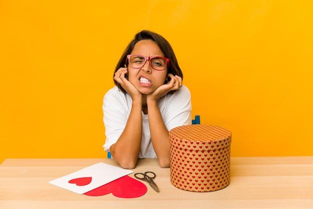 Junge hispanische frau, die ein valentinsgeschenk vorbereitet, isolierte das abdecken der ohren mit den händen.