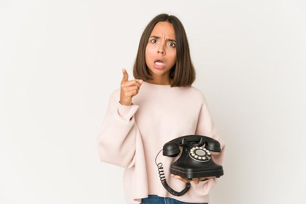 Junge hispanische frau, die ein weinlesetelefon hält, das eine idee, inspirationskonzept lokalisiert.
