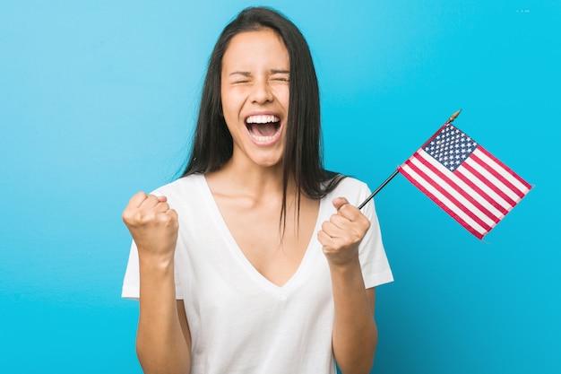Junge hispanische frau, die ein zujubeln der flagge vereinigter staaten sorglos und aufgeregt hält. sieg.