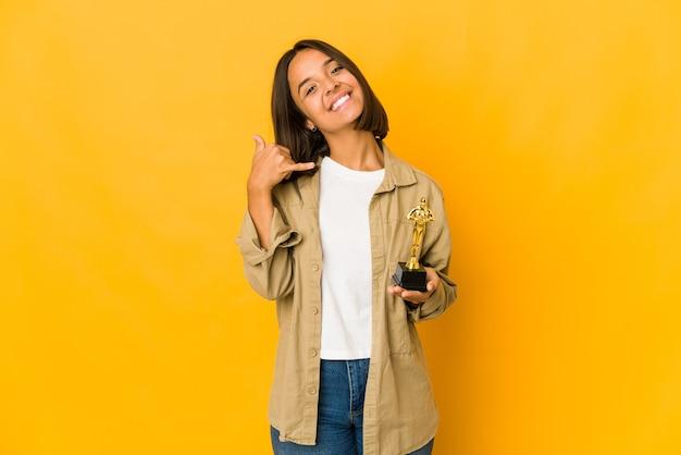 Junge hispanische frau, die eine auszeichnungsstatuette hält, die eine handy-anrufgeste mit den fingern zeigt.