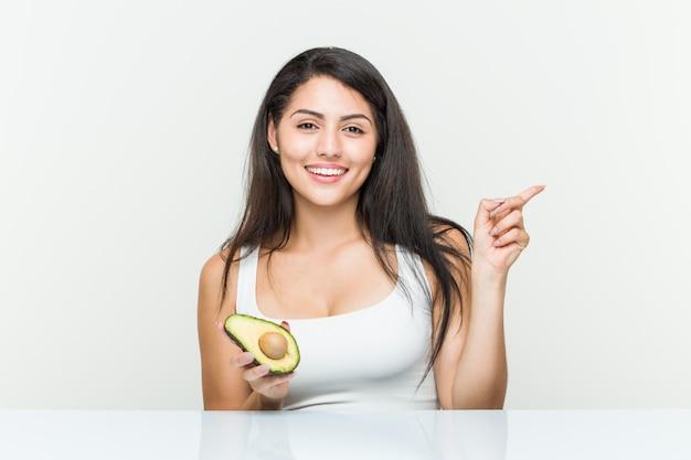 Junge hispanische frau, die eine avocado lächelt hält, freundlich zeigend mit dem zeigefinger weg.