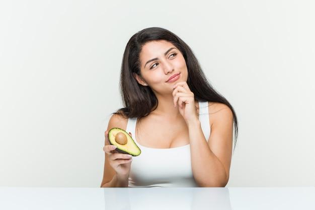 Junge hispanische frau, die eine avocado seitlich schaut mit zweifelhaftem und skeptischem ausdruck hält.