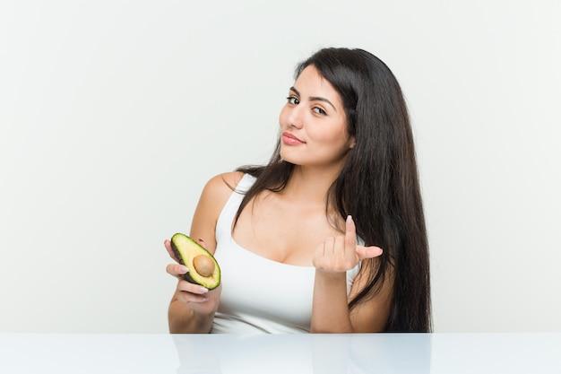 Junge hispanische frau, die eine avocado zeigt mit dem finger auf sie hält, als ob einladung näher kommen.