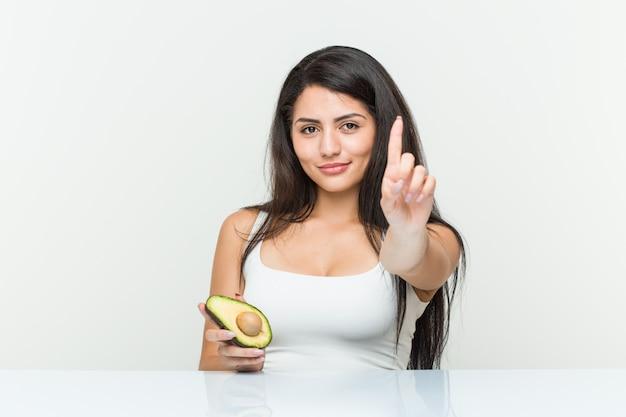 Junge hispanische frau, die eine avocado zeigt nummer eins mit dem finger hält.