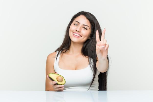 Junge hispanische frau, die eine avocado zeigt nummer zwei mit den fingern hält.