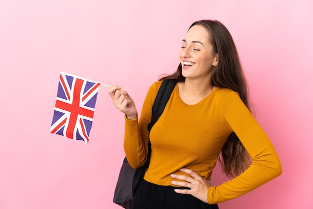 Junge hispanische frau, die eine britische flagge hält, die mit den armen an der hüfte aufwirft und lächelt