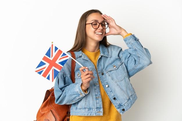Junge hispanische frau, die eine britische flagge über isoliertem weißem hintergrund hält, der viel lächelt