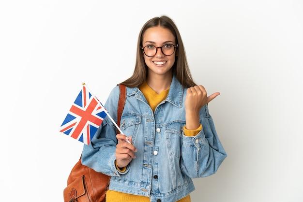 Junge hispanische frau, die eine britische flagge über isoliertem weißem hintergrund hält und auf die seite zeigt, um ein produkt zu präsentieren?