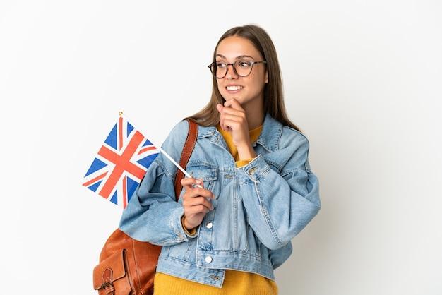Junge hispanische frau, die eine britische flagge über isolierter weißer wand hält und nach oben schaut