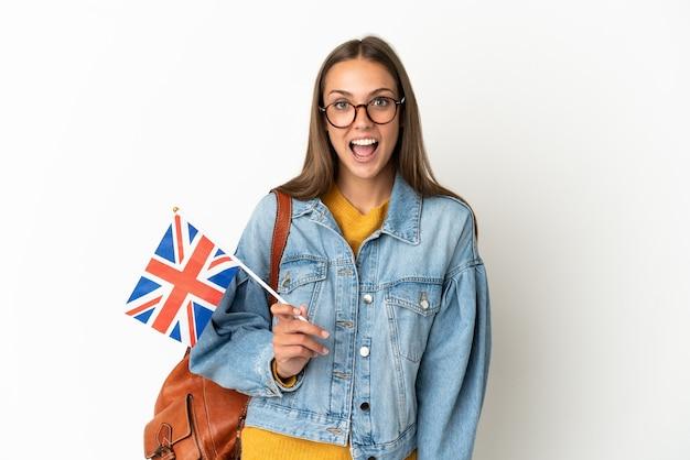 Junge hispanische frau, die eine britische flagge über lokalisiertem weißem hintergrund mit überraschendem gesichtsausdruck hält