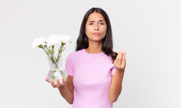 Junge hispanische frau, die eine capice- oder geldgeste macht und ihnen sagt, dass sie mit dekorativen blumen bezahlen sollen?