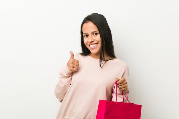 Junge hispanische frau, die eine einkaufstasche lächelt und daumen hochhält