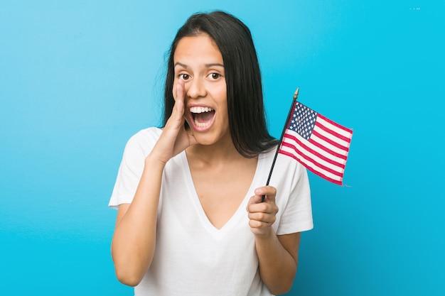 Junge hispanische frau, die eine flagge der vereinigten staaten hält, die aufgeregt nach vorne schreit.
