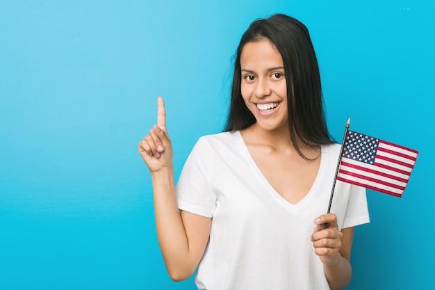 Junge hispanische frau, die eine flagge der vereinigten staaten hält und fröhlich mit zeigefinger weg zeigt.