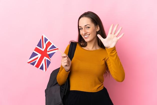 Junge hispanische frau, die eine flagge des vereinigten königreichs hält, die fünf mit den fingern zählt