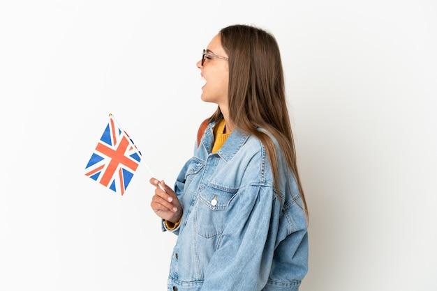 Junge hispanische frau, die eine flagge des vereinigten königreichs über isoliertem weißem hintergrund hält und in seitlicher position lacht