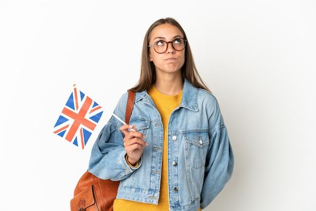Junge hispanische frau, die eine flagge des vereinigten königreichs über isoliertem weißem hintergrund hält und nach oben schaut