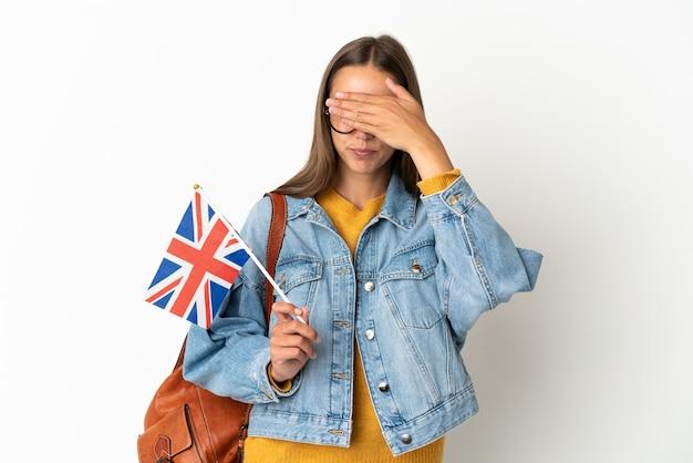 Junge hispanische frau, die eine flagge des vereinigten königreichs über lokalisiertem weißem hintergrund hält, der augen durch hände bedeckt. ich will nichts sehen