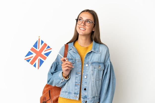 Junge hispanische frau, die eine flagge des vereinigten königreichs über lokalisiertem weißem hintergrund hält, der eine idee beim nachschlagen denkt