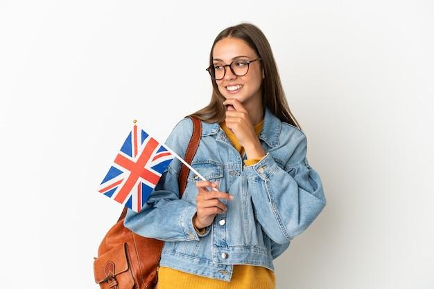 Junge hispanische frau, die eine flagge großbritanniens über lokalisiertem weißem hintergrund hält, der zur seite schaut und lächelt