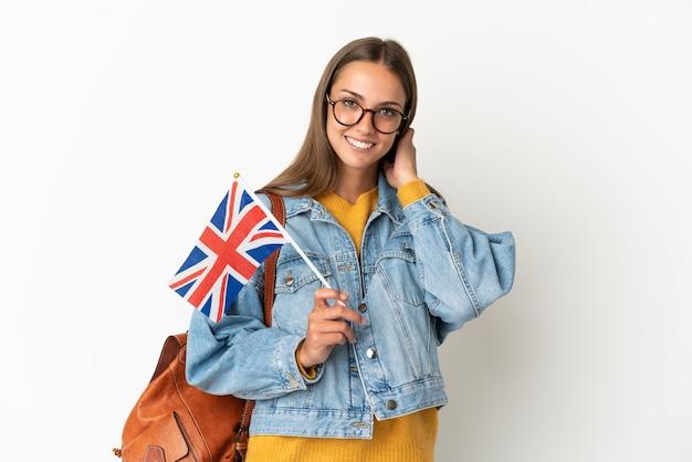 Junge hispanische frau, die eine flagge großbritanniens über lokalisiertem weißem hintergrund hält lachend hält