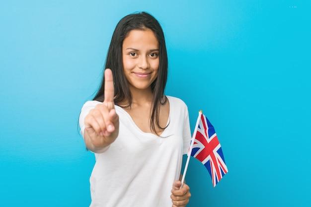 Junge hispanische frau, die eine flagge vereinigten königreichs zeigt nummer eins mit dem finger hält.