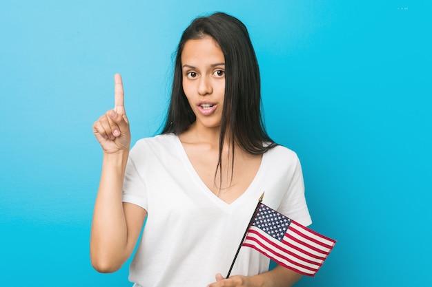 Junge hispanische frau, die eine flagge vereinigter staaten hat irgendeine großartige idee hält