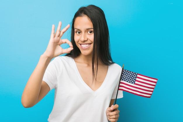 Junge hispanische frau, die eine flagge vereinigter staaten nett und überzeugt hält, okaygeste zeigend