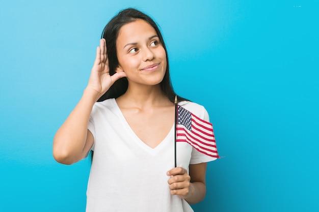 Junge hispanische frau, die eine flagge vereinigter staaten versucht, einen klatsch zu hören hält.