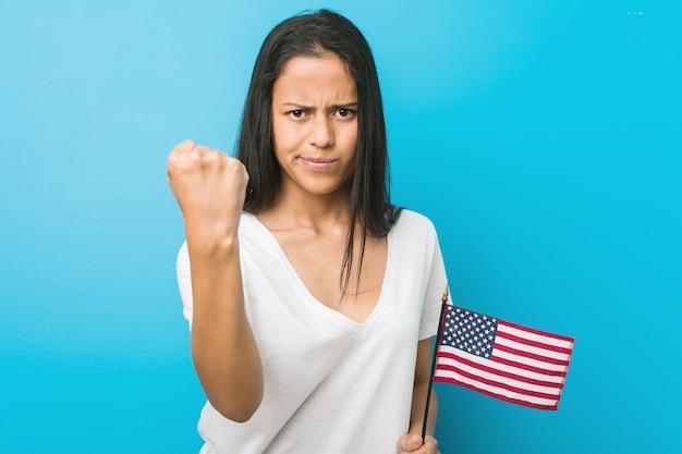 Junge hispanische frau, die eine flagge vereinigter staaten zeigt faust zur kamera, aggressiver gesichtsausdruck hält.