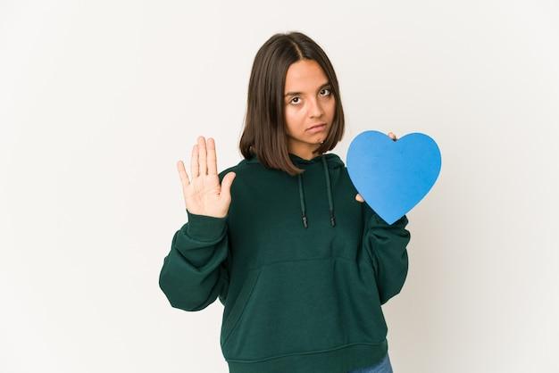 Junge hispanische frau, die eine herzform hält, die mit ausgestreckter hand steht und stoppschild zeigt, das sie verhindert.