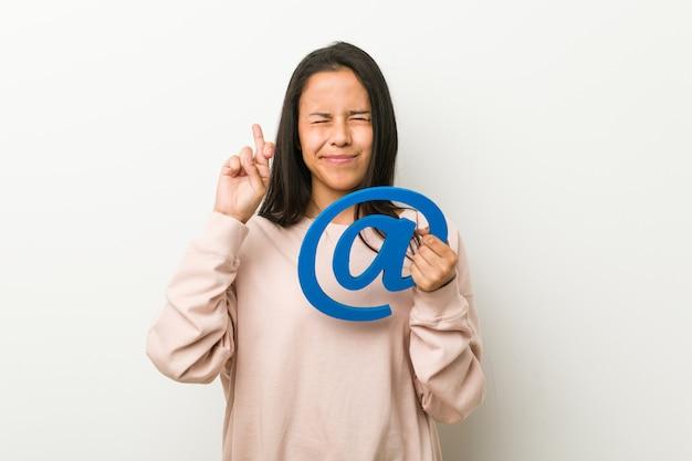 Junge hispanische frau, die eine ikone hält, die finger kreuzt, um glück zu haben