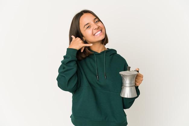 Junge hispanische frau, die eine kaffeemaschine hält, die eine handy-anrufgeste mit den fingern zeigt.