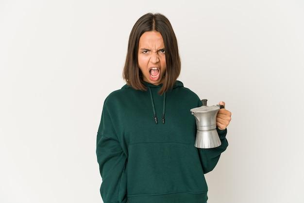 Junge hispanische frau, die eine kaffeemaschine hält, die sehr wütend und aggressiv schreit.