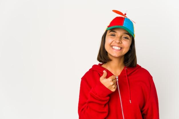 Junge hispanische frau, die eine kappe mit propeller trägt, isoliert lächelnd und daumen hochhebend