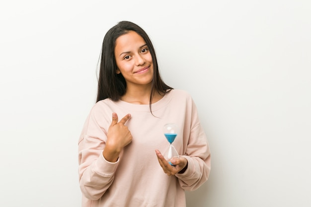 Junge hispanische frau, die eine sanduhr zeigt mit dem finger auf sie hält, als ob einladung näher kommen.