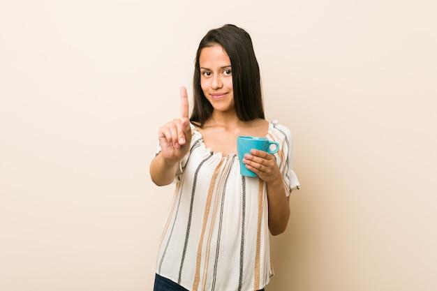Junge hispanische frau, die eine schale zeigt nummer eins mit dem finger hält.