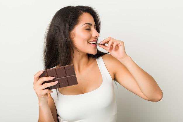 Junge hispanische frau, die eine schokoladentablette hält
