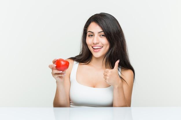 Junge hispanische frau, die eine tomate lächelt und daumen hochhält