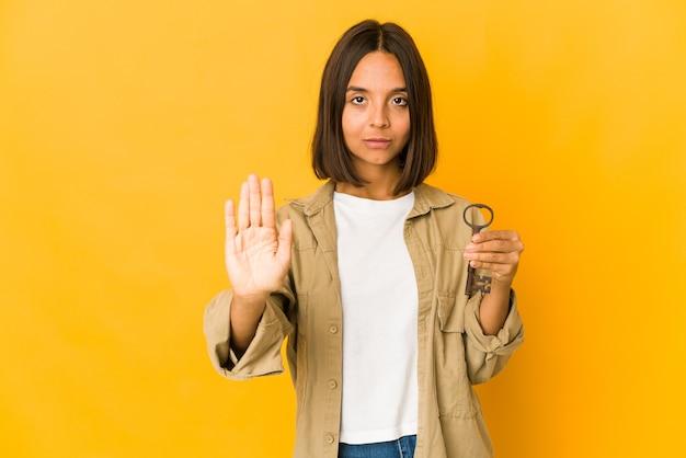 Junge hispanische frau, die einen alten schlüssel hält, der mit ausgestreckter hand steht und stoppschild zeigt, das sie verhindert.