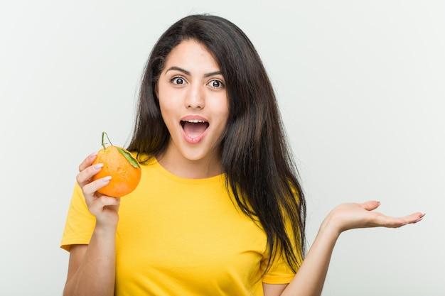 Junge hispanische frau, die einen orange beeindruckten hält, der kopienraum auf handfläche hält.