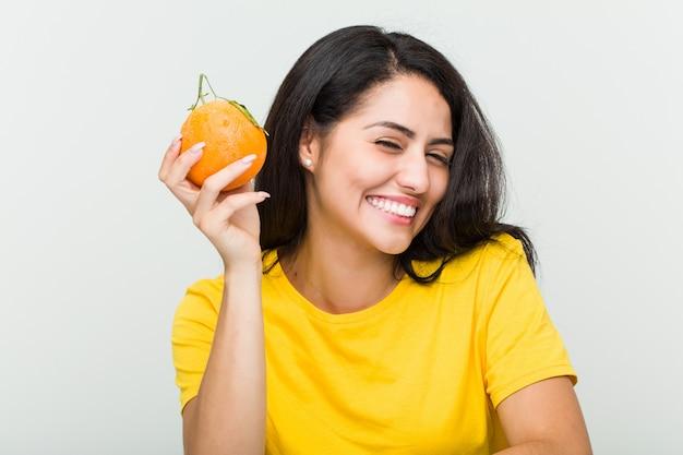 Junge hispanische frau, die einen orangensaft mit einem strohhalm trinkt