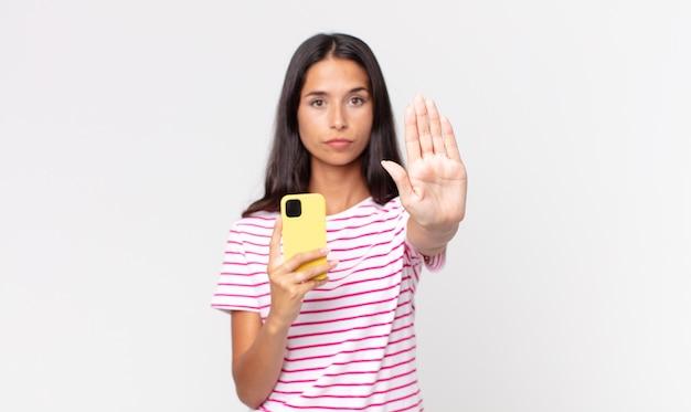 Junge hispanische frau, die ernst aussieht und offene handfläche zeigt, die stopp-geste macht und ein smartphone hält