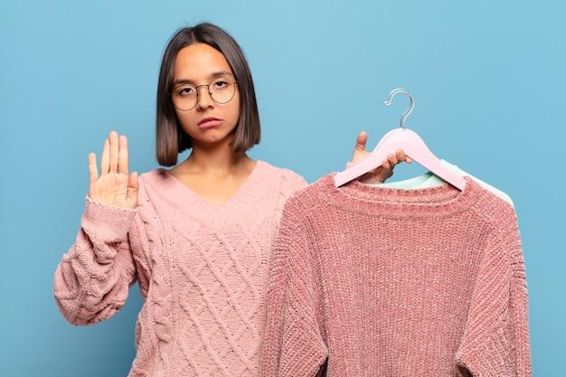 Junge hispanische frau, die ernst, streng, unzufrieden und wütend aussieht und offene handfläche zeigt, die eine stopp-geste macht