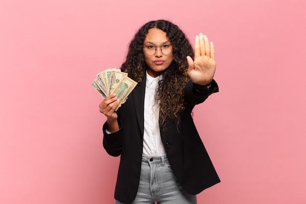 Junge hispanische frau, die ernst, streng, unzufrieden und wütend aussieht und offene handfläche zeigt, die eine stoppgeste macht. dollar-banknoten-konzept