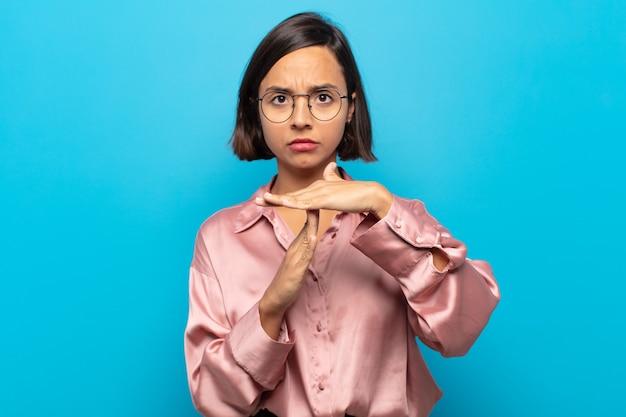 Junge hispanische frau, die ernst, streng, wütend und unzufrieden aussieht und auszeitzeichen macht