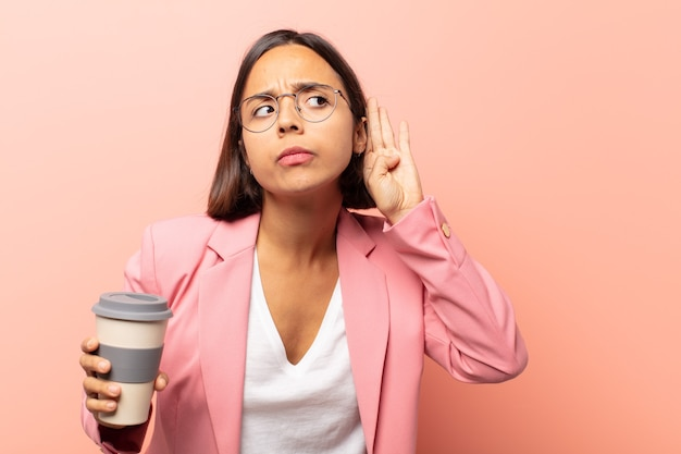Junge hispanische frau, die ernst und neugierig aussieht, zuhört, versucht, ein geheimes gespräch oder einen klatsch zu hören, zu lauschen