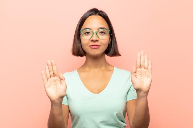 Junge hispanische frau, die ernst, unglücklich, wütend und unzufrieden aussieht und den eintritt verbietet oder mit beiden offenen handflächen stopp sagt