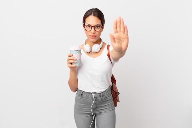 Junge hispanische frau, die ernste offene handfläche zeigt, die stoppgeste macht. studentisches konzept